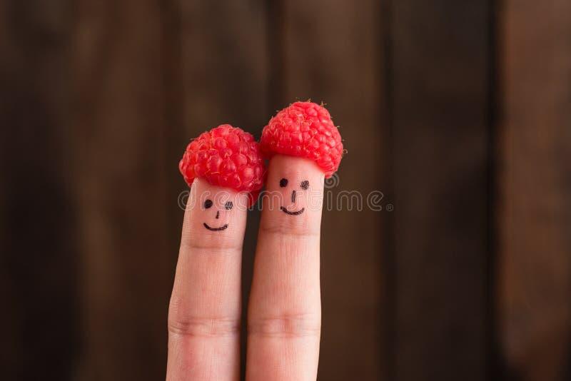 Dos caras sonrientes extraídas en los fingeres en casquillos de la frambuesa fotografía de archivo libre de regalías