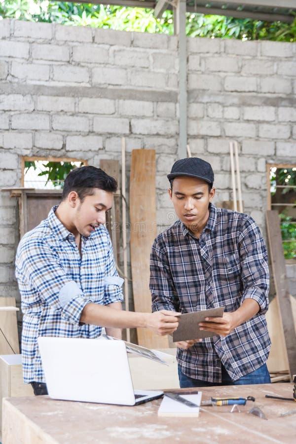 Dos carpinteros jovenes que discuten sobre los materiales de los muebles imagen de archivo