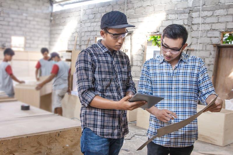 Dos carpinteros jovenes que discuten sobre los materiales de los muebles foto de archivo