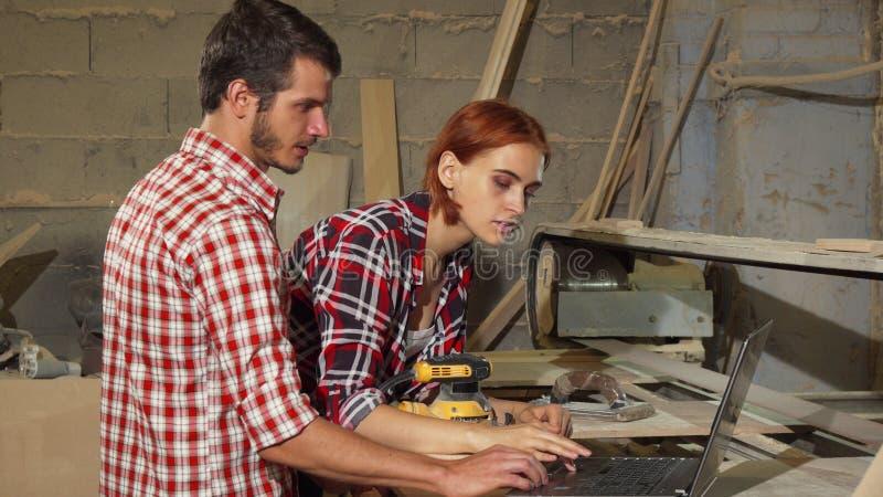 Dos carpinteros que usan el ordenador portátil en su taller mientras que hace los muebles imágenes de archivo libres de regalías