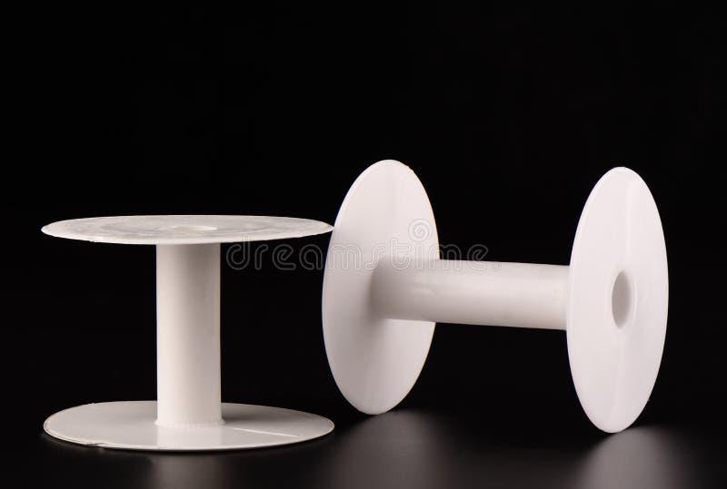 Dos carretes vacíos plásticos de cordón en un fondo negro imagen de archivo libre de regalías