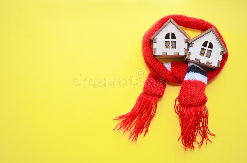 Dos casas de madera con las ventanas en una bufanda roja en un fondo amarillo, casa caliente, aislamiento de casas, copyspace del fotografía de archivo