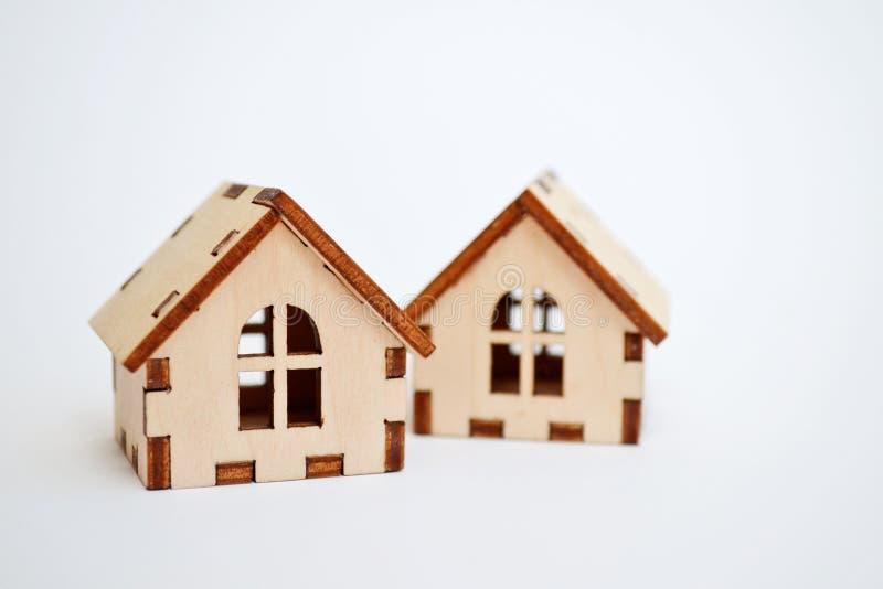 Dos casas de madera en el fondo blanco, soportes detrás de la otra, concepto del juguete de una casa para vender casas con el cop foto de archivo
