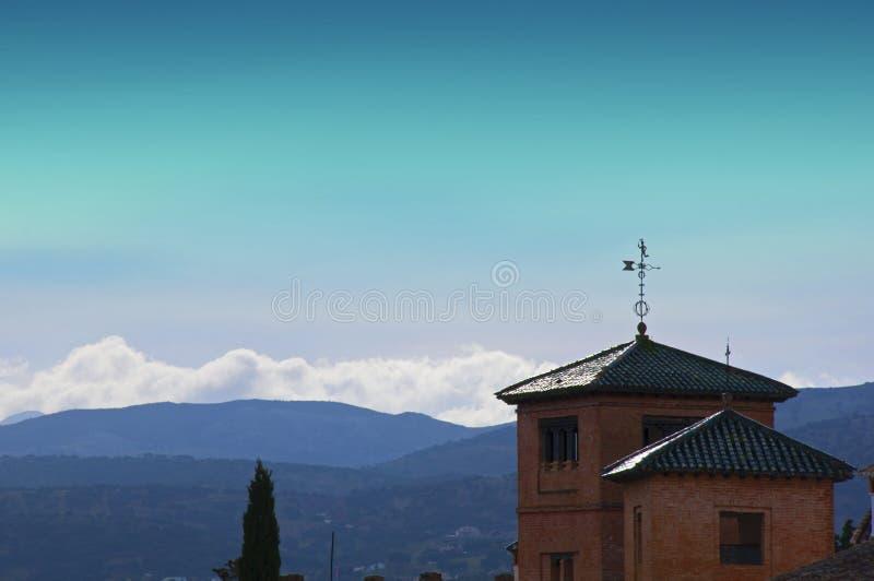Dos casas del ladrillo con los tejados y paleta de tiempo, colinas y montañas, cielo azul fotografía de archivo libre de regalías