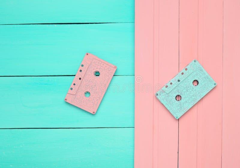Dos casetes audios en un fondo en colores pastel de madera rosado azul foto de archivo