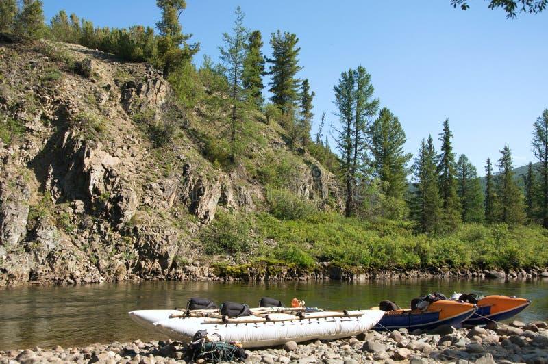 Dos catamaranes inflables en la orilla de un río de la montaña foto de archivo
