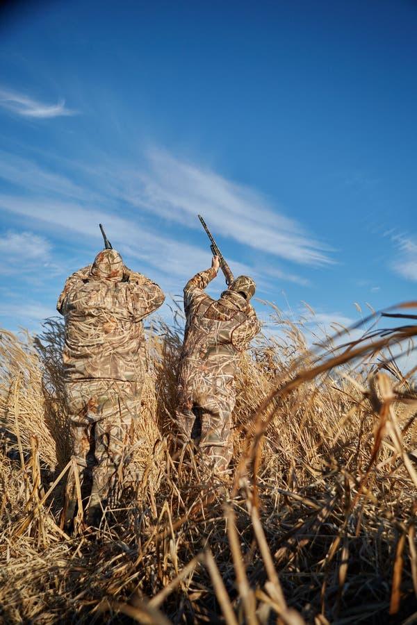 Dos cazadores de las aves acuáticas que apuntan en el cielo con los rifles imágenes de archivo libres de regalías