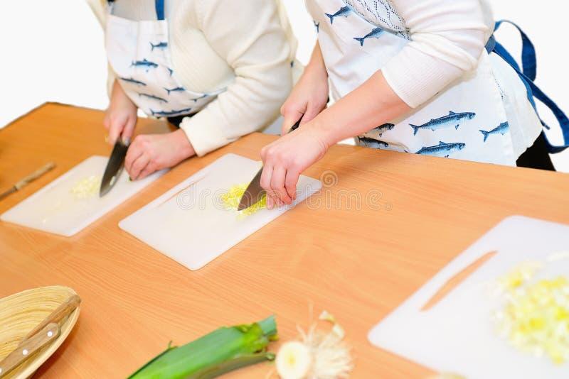 Dos cebollas del corte de la mujer en la tabla de cortar, aislada imagenes de archivo