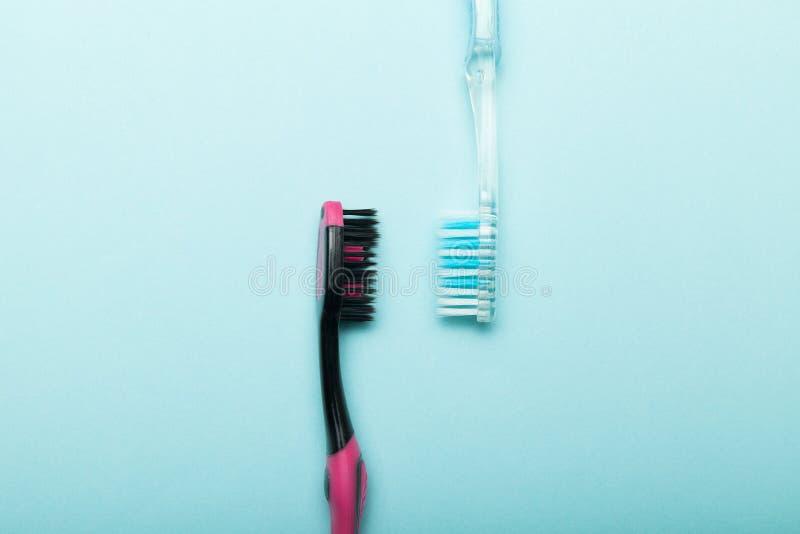 Dos cepillos de dientes en un fondo azul para la higiene de la cavidad bucal fotos de archivo