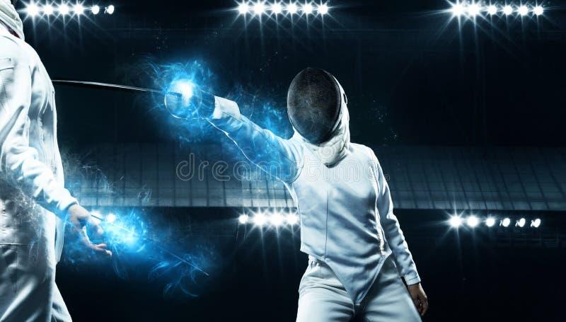 Dos cercadores en la arena deportiva profesional Atletas jovenes que llevan la m?scara y el traje de cercado blanco en duelo en l foto de archivo