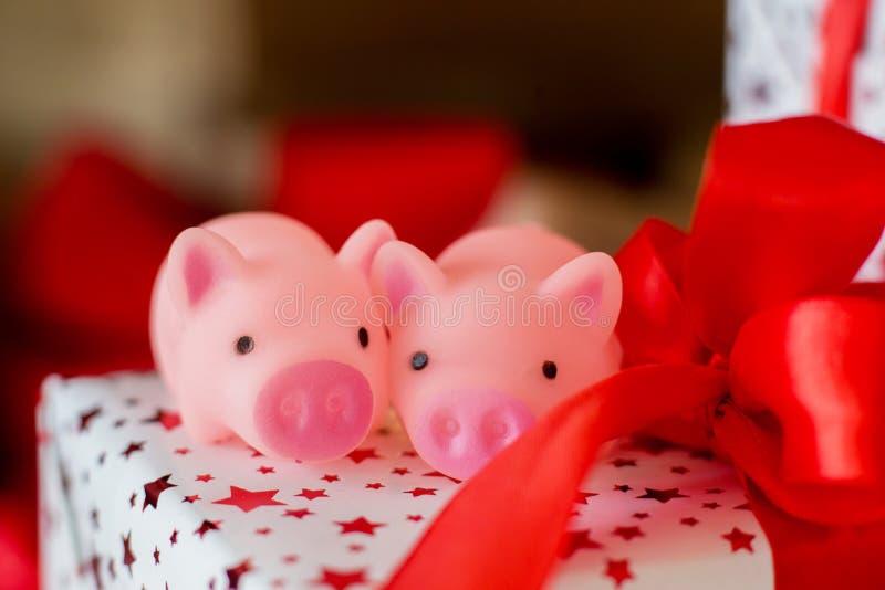 Dos cerdos del juguete se sientan en un regalo del Año Nuevo con un papeleo imagenes de archivo