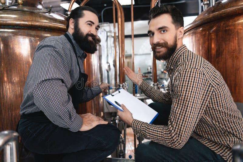 Dos cerveceros profesionales adultos examinan el equipo para saber si hay hacer la cerveza hecha a mano fotografía de archivo libre de regalías