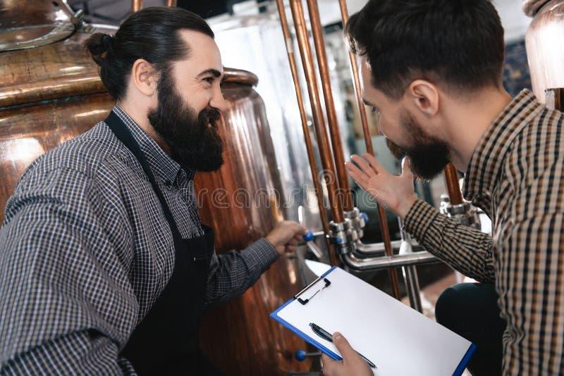 Dos cerveceros profesionales adultos examinan el equipo para saber si hay hacer la cerveza hecha a mano fotos de archivo
