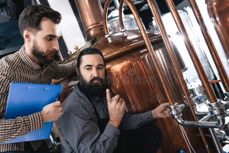 Dos cerveceros profesionales barbudos examinan el equipo para saber si hay hacer la cerveza hecha a mano imagen de archivo