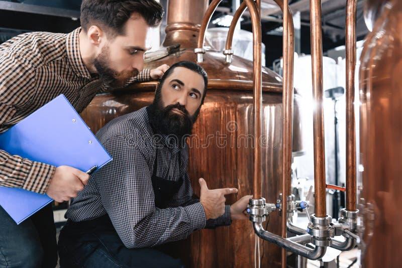 Dos cerveceros profesionales barbudos examinan el equipo para saber si hay hacer la cerveza hecha a mano foto de archivo