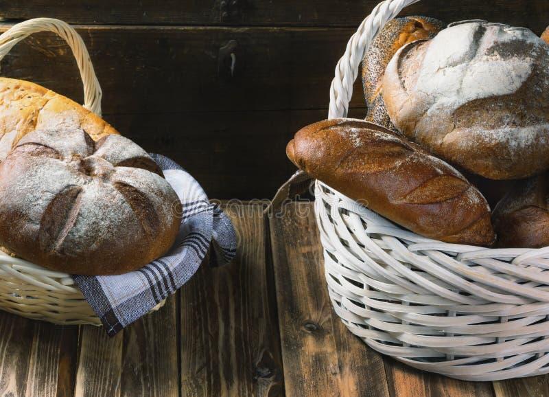 Dos cestas de mimbre con pan fresco en una tabla de madera imagen de archivo