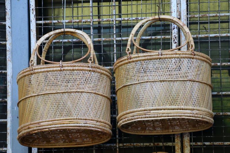 Dos cestas de mimbre que cuelgan en el acero curvado imagenes de archivo
