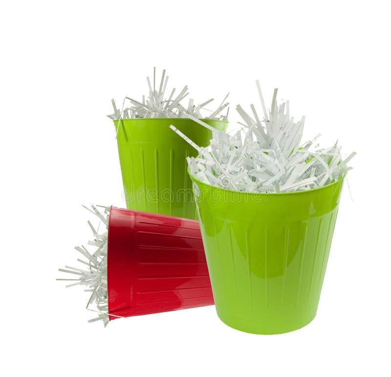 Dos cestas inútiles verdes y una rojas por completo con el papel destrozado fotos de archivo