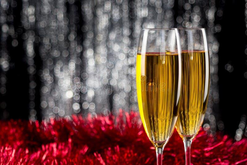 Dos champán o copas de vino con rojo y la decoración de la malla de la Navidad de la plata foto de archivo