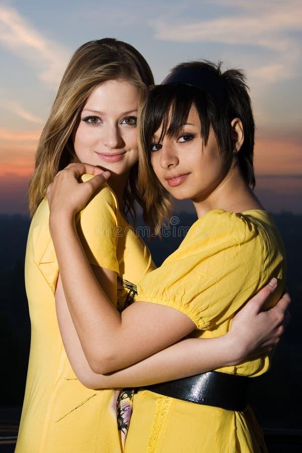 Dos chicas jóvenes atractivas que se abrazan imagen de archivo libre de regalías