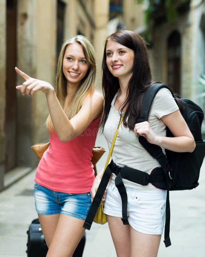 Dos chicas jóvenes con la sonrisa del equipaje Foco en muchacha morena fotografía de archivo