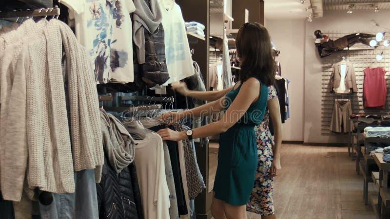 3d1408ce9c3d Dos chicas jóvenes eligen la ropa en tienda. Mercancía, felicidad.