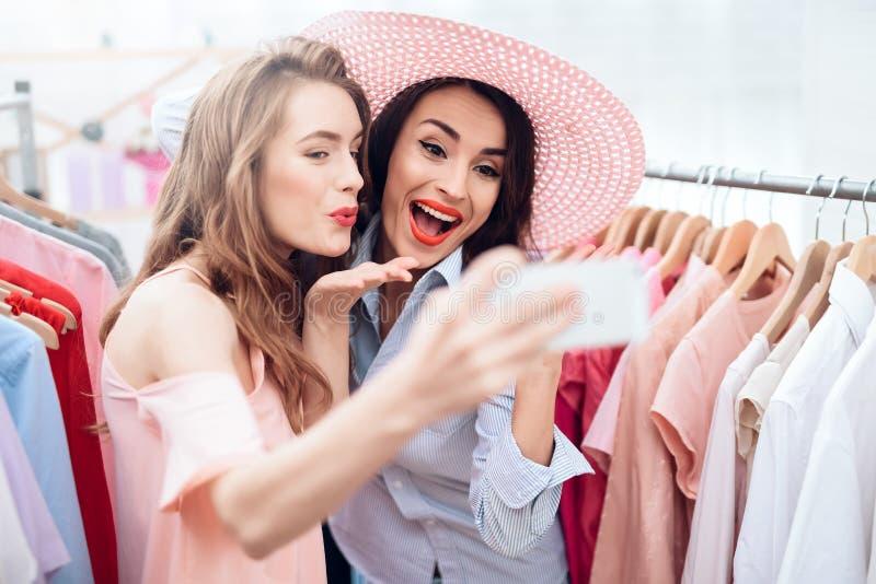 Dos chicas jóvenes en compras Las muchachas eligen la ropa en la tienda Muchachas en la sala de exposición fotos de archivo