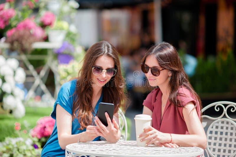 Dos chicas jóvenes en el café del aire libre Dos mujeres después de hacer compras con los bolsos que se sientan en café al aire l imagen de archivo