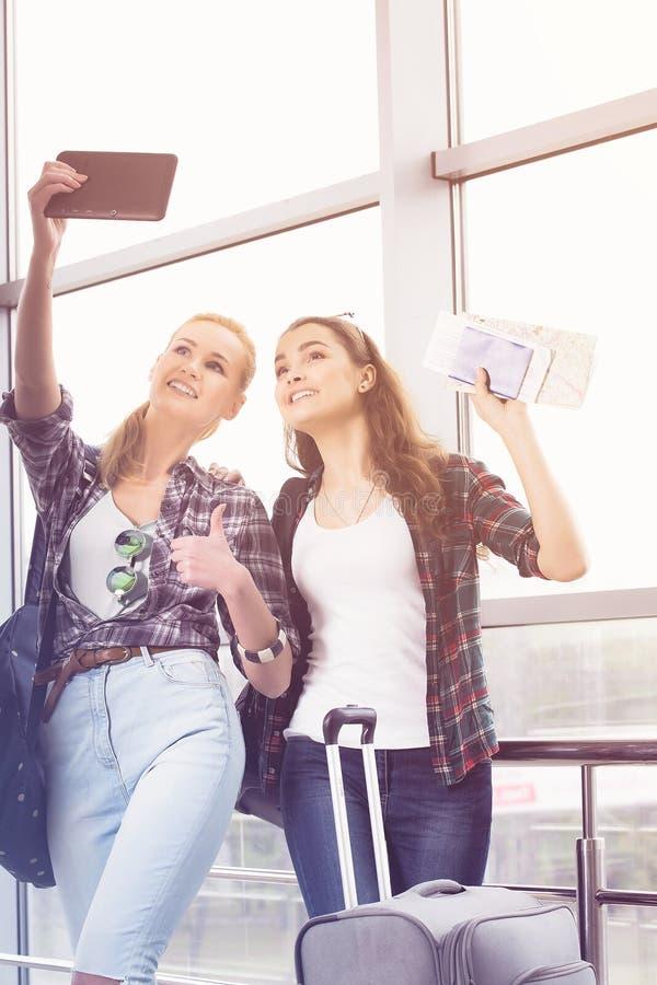 Dos chicas jóvenes en las gafas de sol que hacen el selfie en la tableta del ordenador foto de archivo