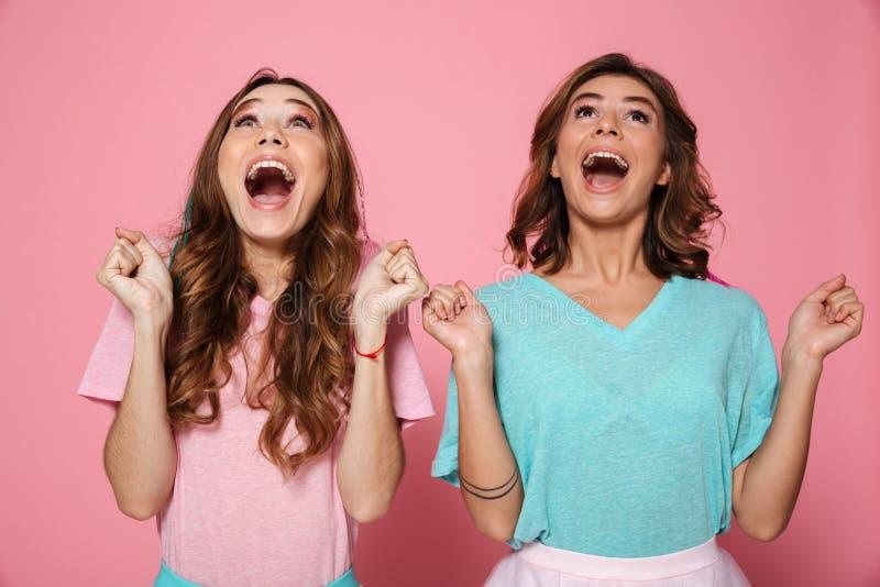 Dos chicas jóvenes extáticas en las camisetas coloridas que muestran ges del ganador foto de archivo