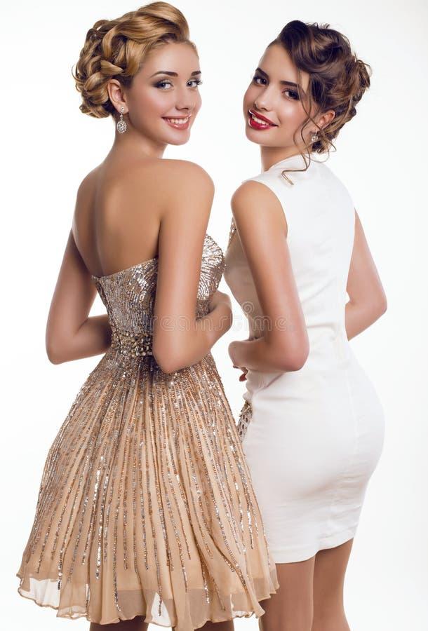 dos chicas jóvenes hermosas en vestidos elegantes imagen de archivo libre de regalías