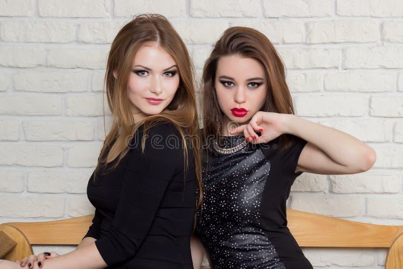 dos chicas jóvenes hermosas en vestidos negros se sientan en el banco y el chisme imagenes de archivo