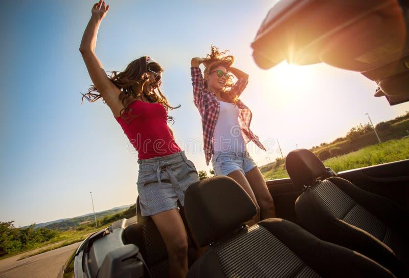Dos chicas jóvenes hermosas que bailan en un convertible imagen de archivo