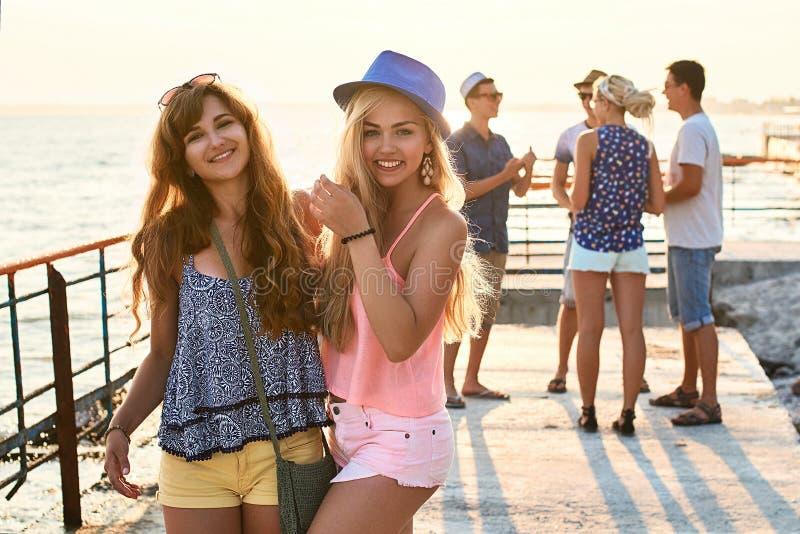 Dos chicas jóvenes hermosas que se divierten en la playa de la tarde con el grupo de sus amigos en fondo imagenes de archivo