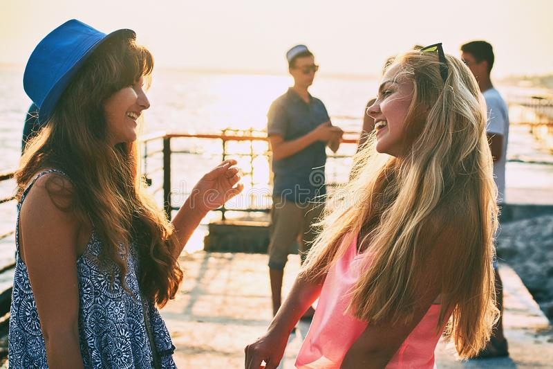 Dos chicas jóvenes hermosas que se divierten en la playa de la tarde con el grupo de sus amigos en fondo fotografía de archivo libre de regalías