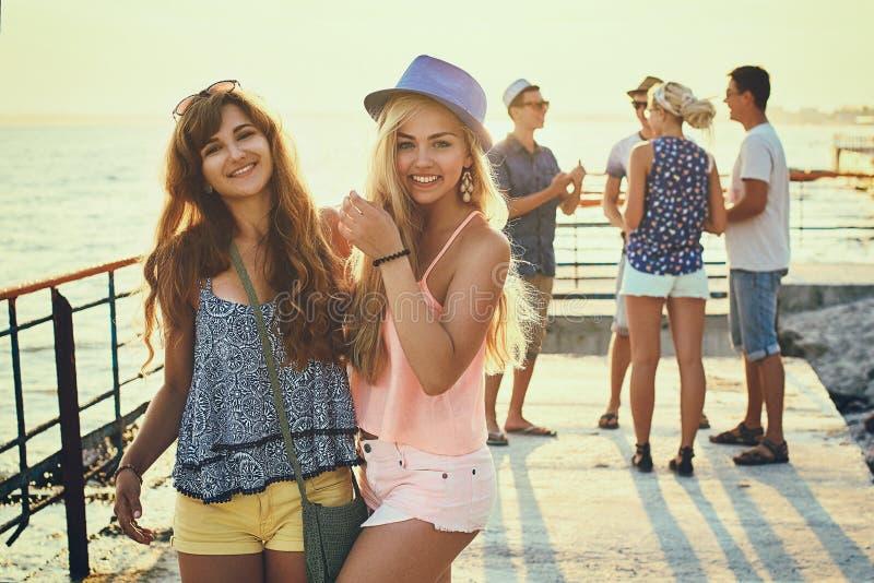 Dos chicas jóvenes hermosas que se divierten en la playa de la tarde con el grupo de sus amigos en el fondo entonado en vintage fotos de archivo libres de regalías