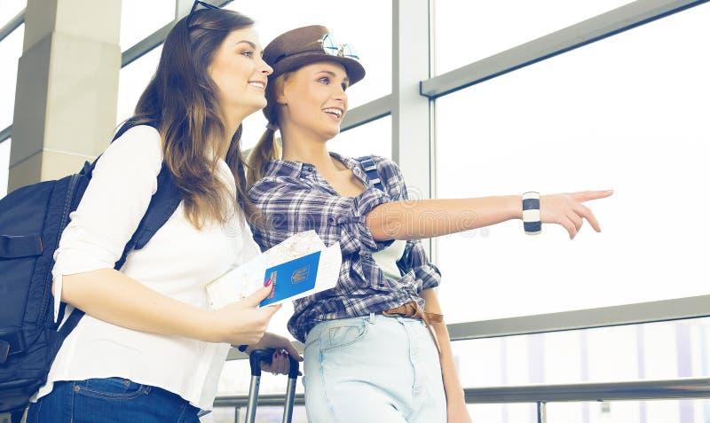 Dos chicas jóvenes miran el mapa y muestran la dirección del dedo índice foto de archivo