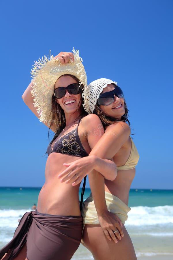 Dos chicas jóvenes o amigos atractivos que juegan en una playa asoleada en vaca foto de archivo libre de regalías