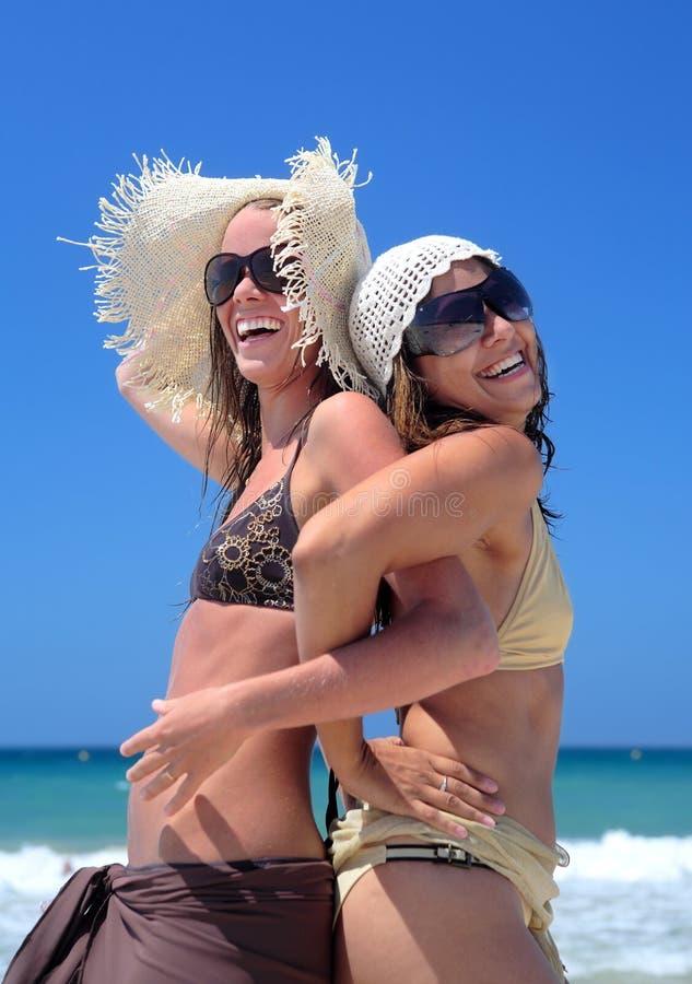 Dos chicas jóvenes o amigos atractivos que juegan en una playa asoleada en vaca imagen de archivo libre de regalías