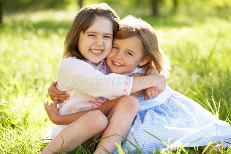 Dos chicas jóvenes que abrazan en campo del verano foto de archivo