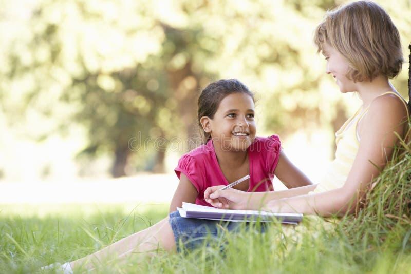 Dos chicas jóvenes que bosquejan en el campo que se inclina contra árbol imagen de archivo