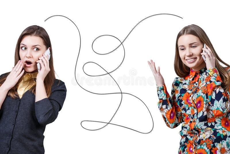 Dos chicas jóvenes que hablan por los teléfonos celulares foto de archivo libre de regalías