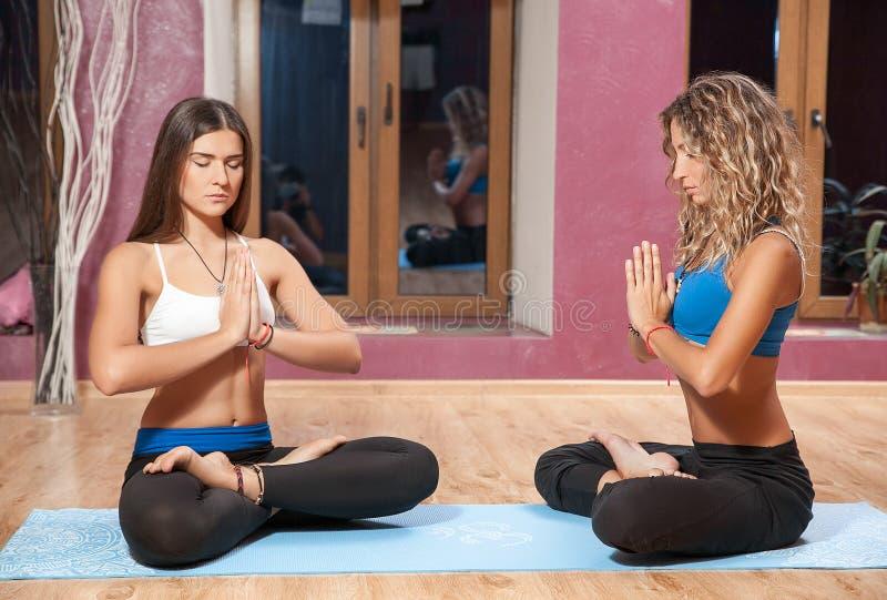 Dos chicas jóvenes que hacen yoga en la estera dentro fotografía de archivo libre de regalías