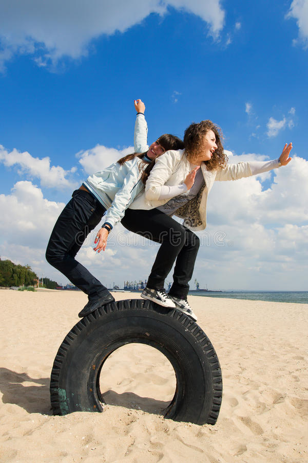 Dos chicas jóvenes que se divierten en la playa imagen de archivo libre de regalías