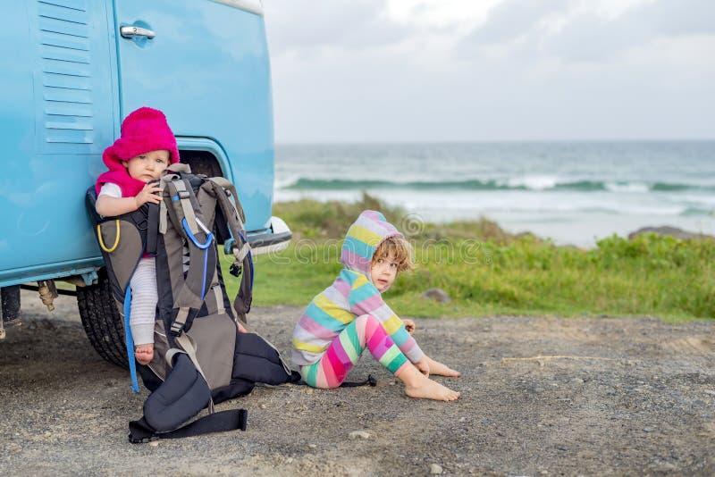 Dos chicas jóvenes que se sientan al lado del campista del minivan del viejo estilo imagenes de archivo