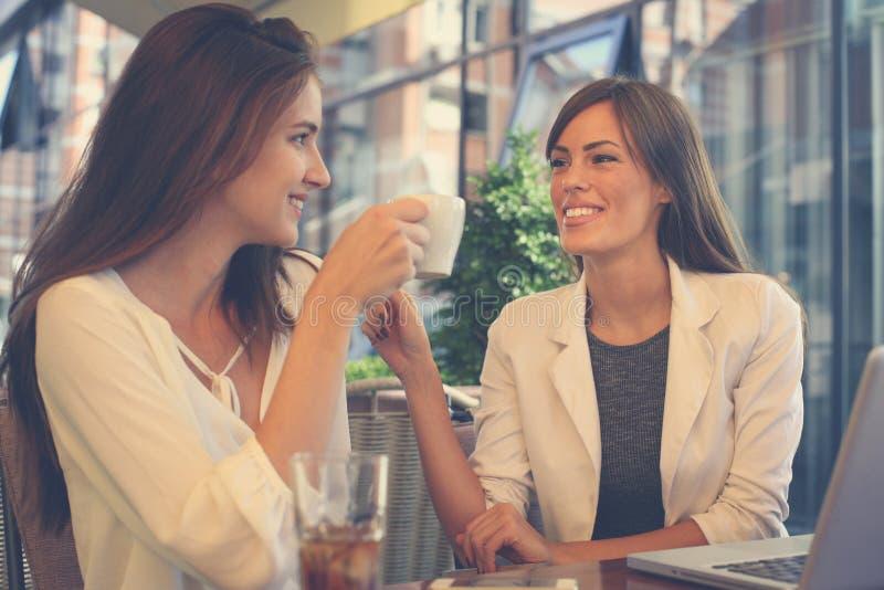 Dos chicas jóvenes que se sientan en café de consumición del café y que tienen conve imágenes de archivo libres de regalías