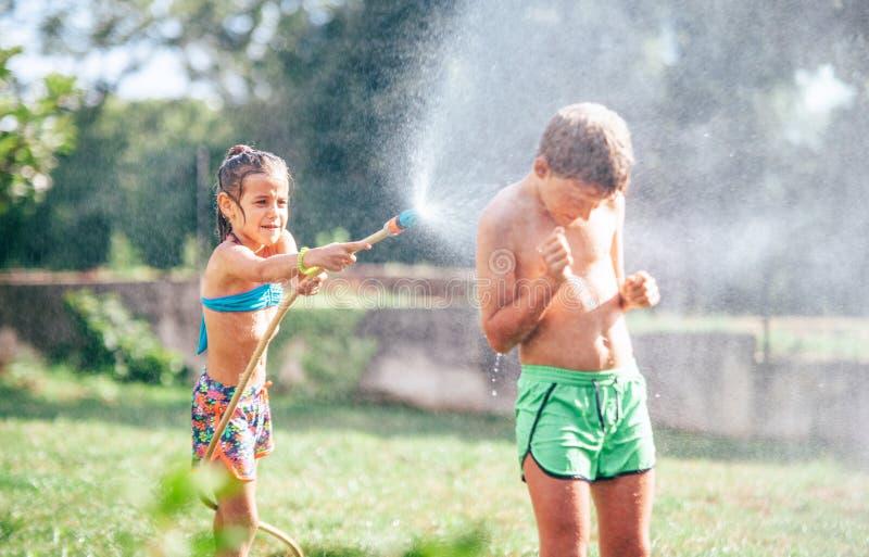 Dos childs que juegan en jardín, se vierten de la manguera, hacen una lluvia Imagen feliz del concepto de la niñez foto de archivo