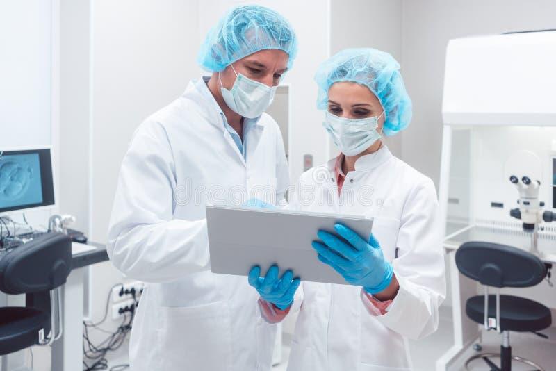 Dos científicos que trabajan junto en el laboratorio que mira datos imagenes de archivo