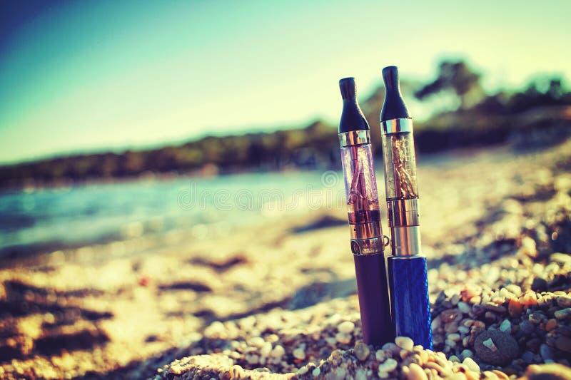 Dos cigarrillos electrónicos pegados en arena foto de archivo