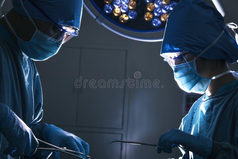 Dos cirujanos que miran abajo y que trabajan en la mesa de operaciones, sala de operaciones oscura foto de archivo